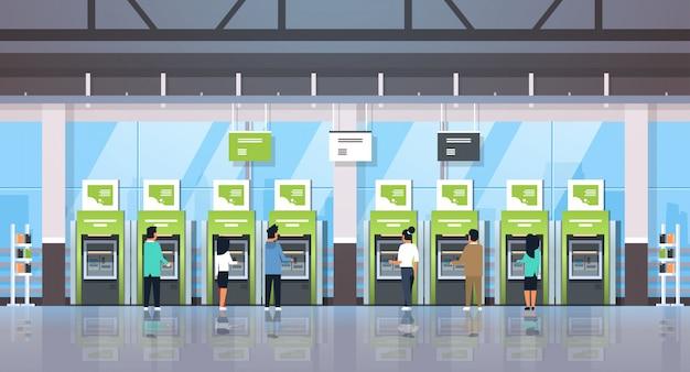Personas que usan terminales de pago en cajeros automáticos