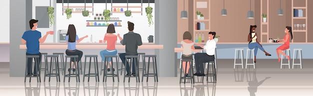 Personas sentadas en taburetes en el bar