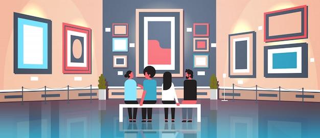 Personas turistas visitantes en el interior del museo de la galería de arte moderno sentado en un banco mirando pinturas contemporáneas, obras de arte o exhibiciones