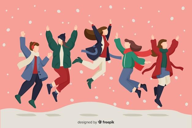Personas vestidas con ropa de invierno saltando en la nieve.
