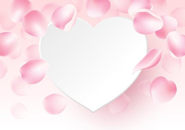 Pétalos de rosa cayendo con corazón de papel en blanco.