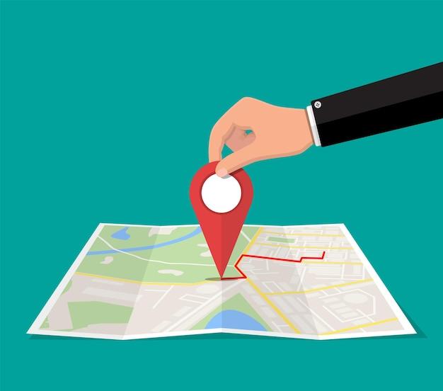 Pin de ubicación en mano y mapa de papel