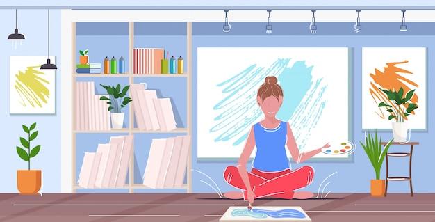 Pintora con pincel y paleta mujer artista sentado lotus pose dibujo imagen concepto moderno estudio de arte interior horizontal