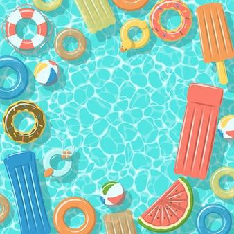Piscina desde la vista superior con coloridos anillos de goma inflables, balsas, pelota de playa y salvavidas.