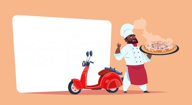 Pizza delivery concept african american chef cook hold box con plato caliente de pie en la plantilla de bicicleta de motor roja banner con espacio de copia