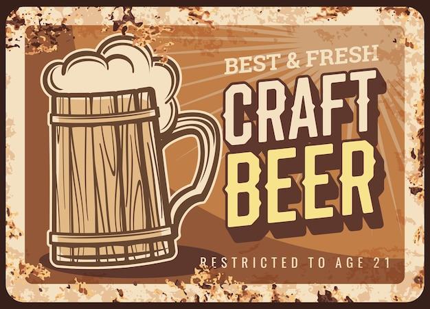 Placa de metal oxidado de cerveza artesanal. jarra antigua de madera con mango, espuma de cerveza y tipografía. banner retro de cervecería local, pub o bar, cartel publicitario con textura de óxido