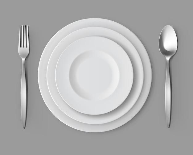Placas redondas vacías blancas con tenedor y cuchara.
