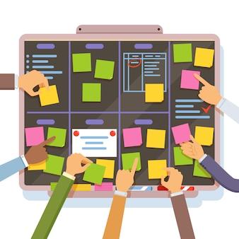 Plan de proyecto ágil. manos que sostienen y ponen notas en el tablero de planificación.