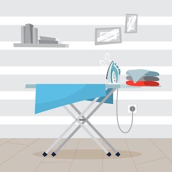 Plancha y pila de ropa en la tabla de planchar.