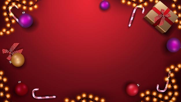 Plantilla para banner o postal de navidad. plantilla roja con bolas de navidad, bastones de caramelo, guirnaldas y regalos, vista superior