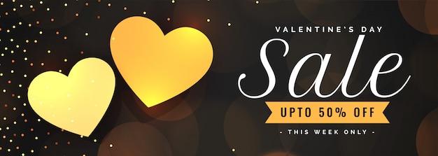 Plantilla de banner de venta del día de san valentín con dos corazones dorados