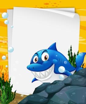 Plantilla de papel en blanco con un personaje de dibujos animados de tiburón en la escena submarina
