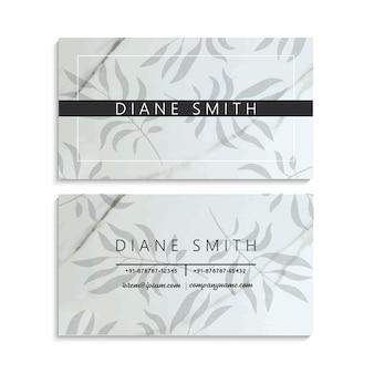 Plantilla de tarjeta de visita de mármol de lujo con hojas tropicales.