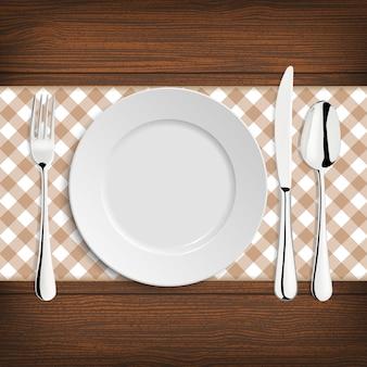 Plato con cuchara, khife y tenedor sobre una mesa de madera