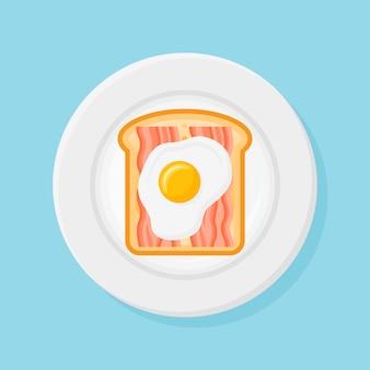 Plato con pan tostado, tiras de tocino y huevo frito en estilo plano.