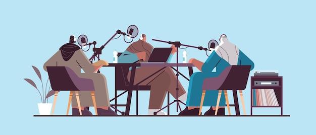 Podcasters árabes hablando con micrófonos que graban podcasts en el concepto de transmisión de radio en línea de podcasting de estudio