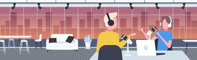 Podcasters hablando con micrófonos grabando podcast en estudio podcasting concepto de radio en línea hombre en auriculares entrevistando a mujer retransmitiendo retrato horizontal