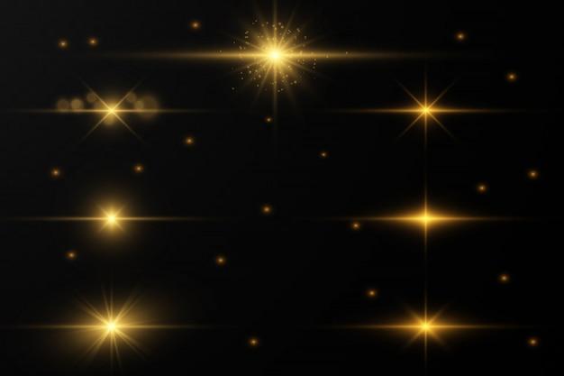 El polvo chispea y las estrellas doradas brillan con una luz especial. brilla en un fondo transparente. efecto de luz navideña.