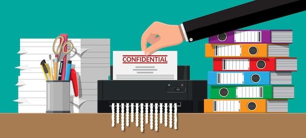 Poner papel de documento en la máquina trituradora de la mano. documento rasgado en pedazos.