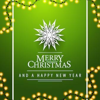 Postal cuadrada verde feliz navidad y feliz año nuevo con guirnaldas y copos de nieve de papel