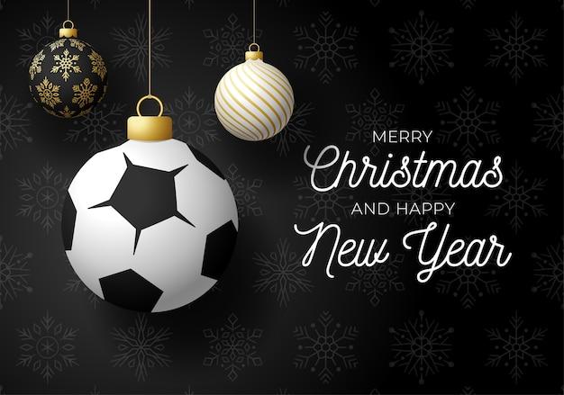 Postal deportiva de lujo feliz navidad y próspero año nuevo. balón de fútbol como una bola de navidad sobre fondo negro.