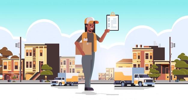 Posttwoman en uniforme con caja de paquete de cartón y recibir el formulario de servicio de entrega urgente de mensajería afroamericana concepto moderno calle de la ciudad paisaje urbano de fondo plano de longitud completa