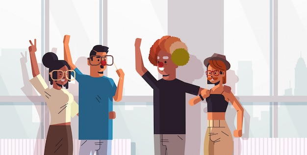 Primer día de los inocentes mezcla de raza colegas con gafas divertidas bigote y sombrero de payaso concepto de celebración de vacaciones moderno retrato horizontal interior de la oficina