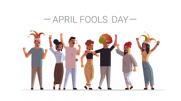 Primer día de los inocentes raza mixta personas con divertidos sombreros de bufón gafas bigote y sombrero de payaso concepto de celebración festiva hombres mujeres grupo de pie juntos cartel horizontal longitud completa