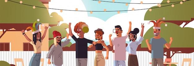 Primer día de los inocentes raza mixta personas con sombreros de bufón divertidos gafas bigote y sombrero de payaso concepto de celebración de vacaciones patio trasero de la casa paisaje horizontal fondo
