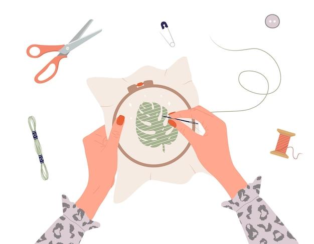 Proceso de bordado. manos femeninas con hilo y aguja.