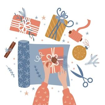 Proceso de envolver cajas de regalo de navidad dos manos femeninas preparándose para la celebración de la víspera de navidad o ...