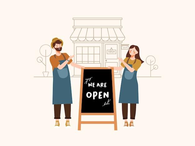 Los propietarios de pequeñas empresas se paran para saludar a los compradores con el cartel de pizarra abierta