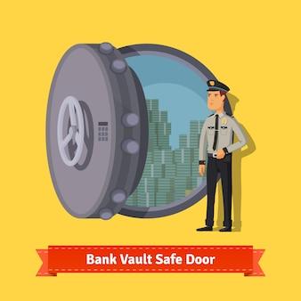 Puerta de la caja fuerte de la bóveda del banco con un protector del oficial