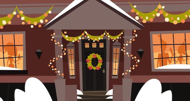 Puerta de la casa decorada con guirnaldas, edificio de vacaciones de invierno, feliz navidad y feliz año nuevo concepto