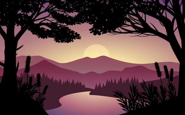 Puesta de sol en el bosque con la silueta del árbol y el río