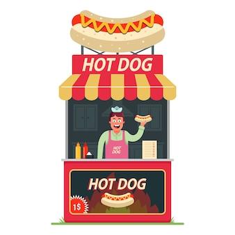 Un puesto de perritos calientes con un vendedor alegre dentro. comida rápida en la calle.
