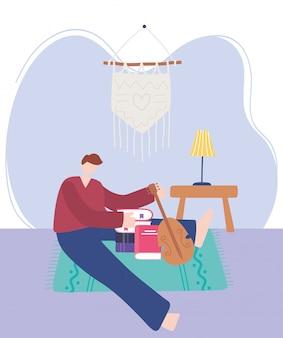 Quedarse en casa, joven con libro y violín sentado en el piso, autoaislamiento, actividades en cuarentena por coronavirus