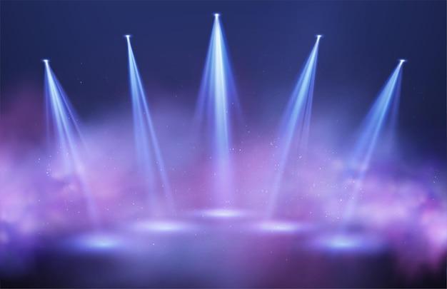 Rayos de luz de focos en bocanadas de humo púrpura y azul