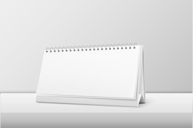 Realista horizontal en blanco espiral calendario closeup de pie sobre la mesa blanca. plantilla de diseño