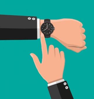 Reloj de pulsera a mano. el hombre verifica la hora.