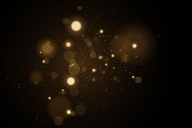 Resumen luces doradas bokeh sobre un fondo negro.
