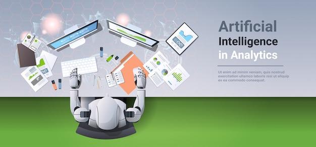 Robot moderno sentado en el lugar de trabajo humanoide analizando gráficos financieros diagramas analítica de negocios
