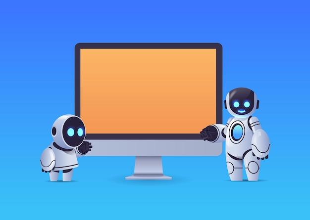 Robots modernos de pie cerca del monitor de la computadora con tecnología de inteligencia artificial de carácter robótico de pantalla en blanco