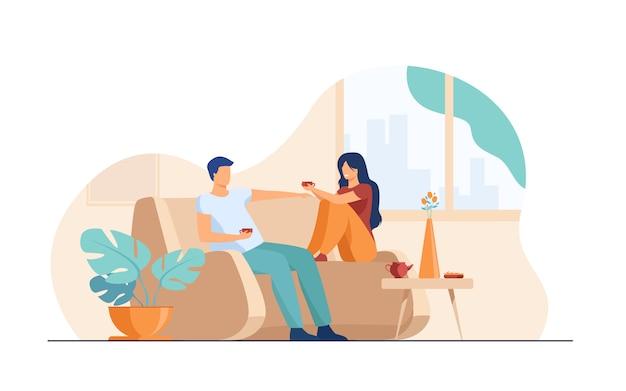 Romántica pareja sentada en el sofá, hablando y tomando café