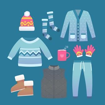 Ropa de invierno plana y elementos esenciales con una taza de chocolate caliente.