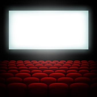 Sala de cine con pantalla y asientos rojos.