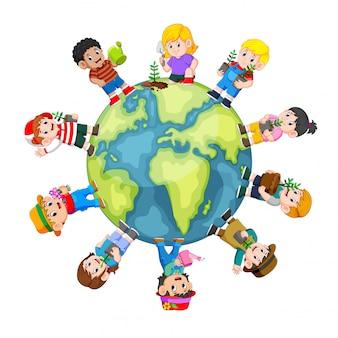 Salvar el concepto de la tierra con niños felices con una planta verde joven