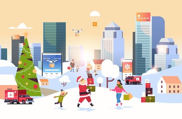 Santa claus llevando cajas de regalo personas con bolsas de compras caminando al aire libre preparándose para navidad año nuevo vacaciones hombres mujeres usando aplicación móvil en línea fondo de paisaje de invierno