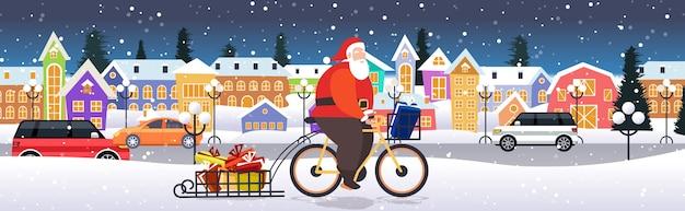 Santa claus montando bicicleta con cajas de regalo en trineo feliz navidad vacaciones de invierno concepto de celebración paisaje urbano nevadas