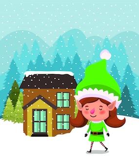 Santa elfo ayudante con casa en paisaje nevado